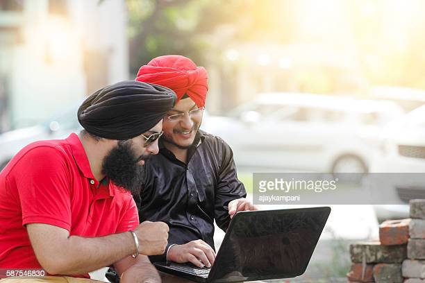 two sikh men using laptop - punjab india stock pictures, royalty-free photos & images