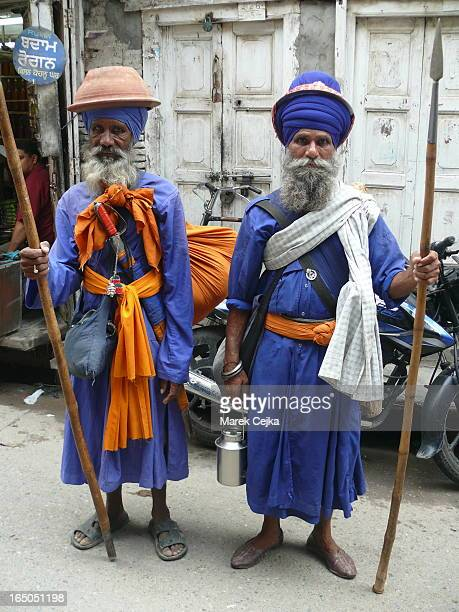 Two Sikh pilgrims in Sikhl holy city Amritsar. Note the main Sikh colours: blue and orange and ancient weapons. The knife or sword is one of the main...