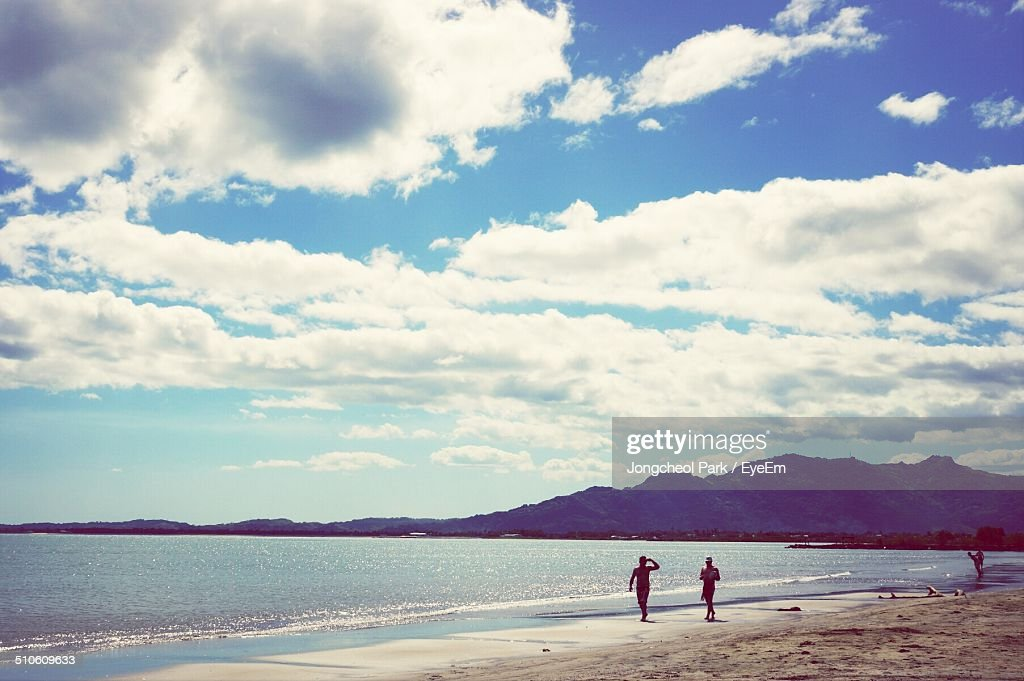 Two silhouette people walking on beach : Stock Photo