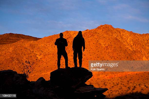 Two silhouetted male backpackers pose for a portrait while standing on a rock pile while hiking through Death Valley's Confidence Hills, California.