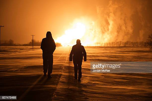 Two silhouettes walking towards the TransCanada pipeline explosion in Otterburne, Manitoba on January 25, 2014.