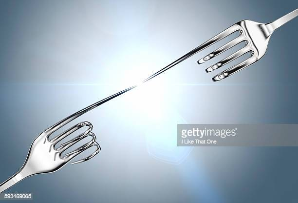 two silver forks reaching out to each other - atomic imagery stock pictures, royalty-free photos & images