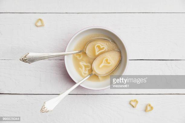 Two silver spoons in bowl of chicken soup with heart-shaped noodles