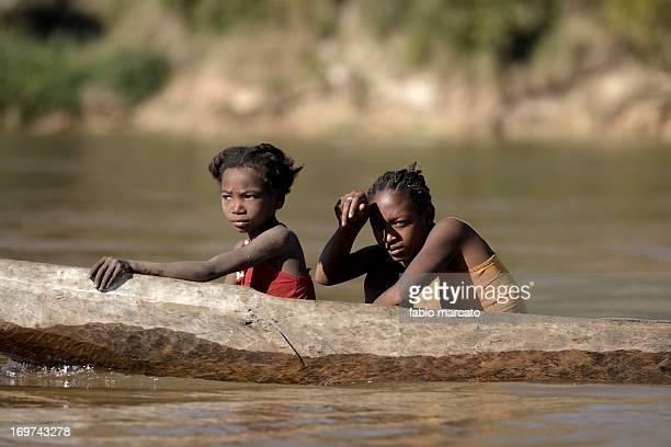 Two sister cross the Tsiribihina river in canoe