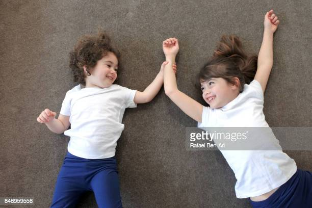 Two sister girls plays together at home on the carpet