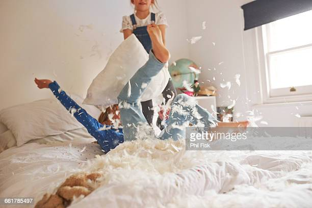 two sister having feather pillow fight on bed - rivaliteit stockfoto's en -beelden
