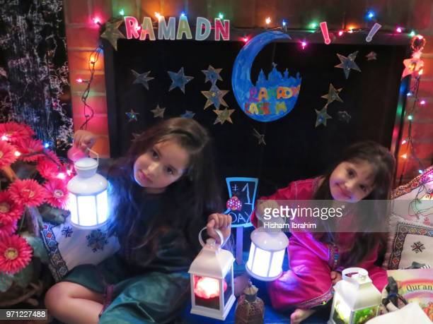 Two sisters 3 years and 6 years old celebrating Ramadan, holding Ramadan lanterns.