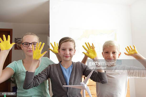 two sisters and brother with yellow sunshine hands and a model of wind turbine - sigrid gombert fotografías e imágenes de stock