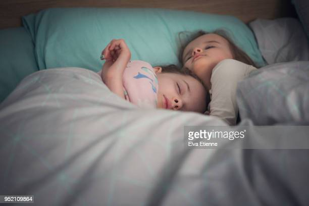 Two sisters asleep in bed