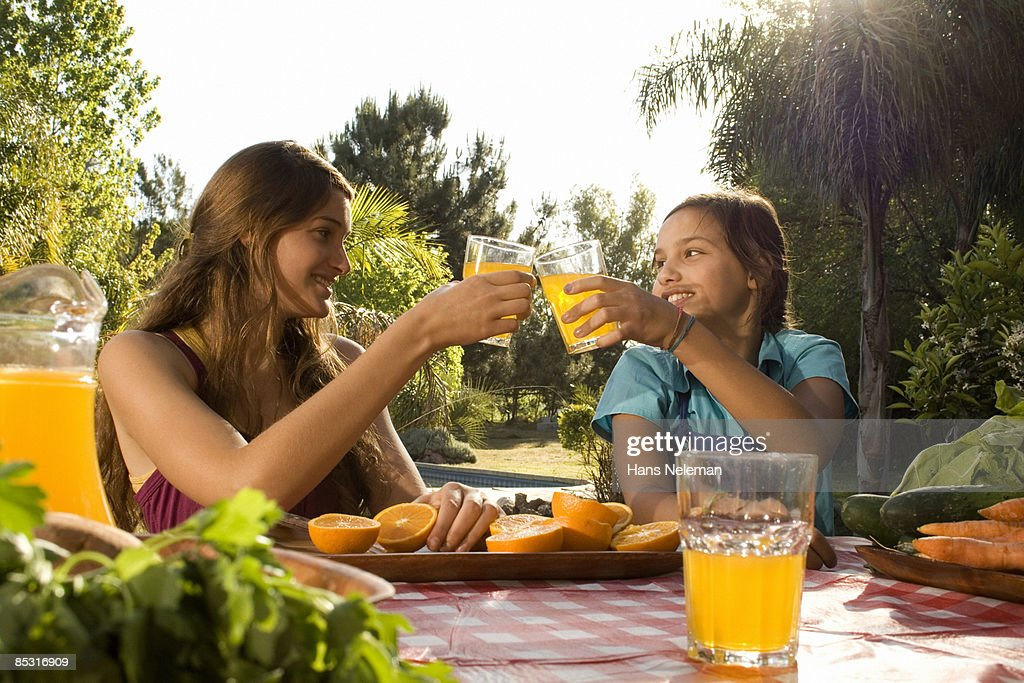 Two sisters celebrating the orange juice they made : Stock Photo