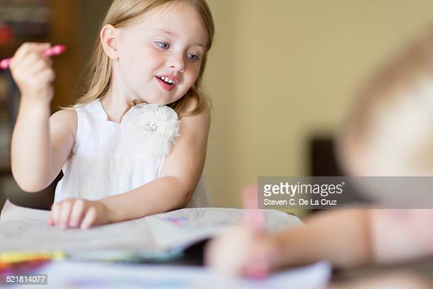Two sisters coloring in books with crayons in sitting room