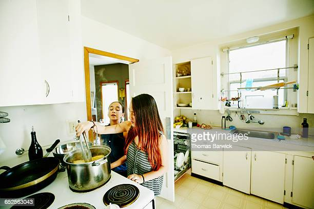 Two sisters cooking corn on stove in home kitchen