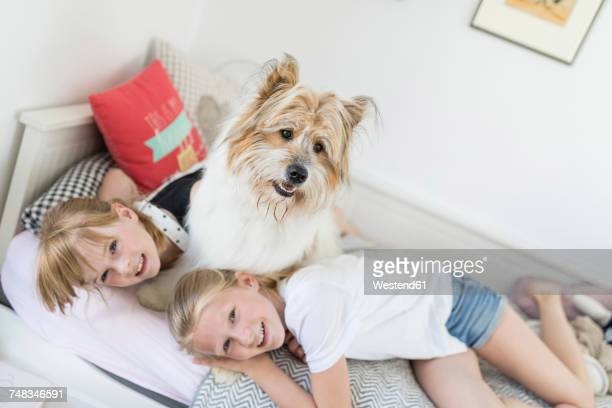 Two sisters cuddling with dog in bed