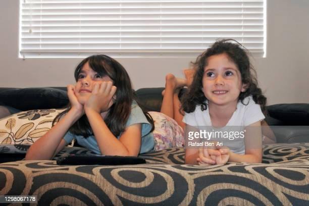 two sisters girls watching tv together - rafael ben ari - fotografias e filmes do acervo