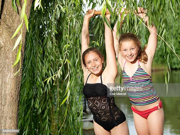 two sisters hanging on swing beside lake - swimwear stock photos and pictures