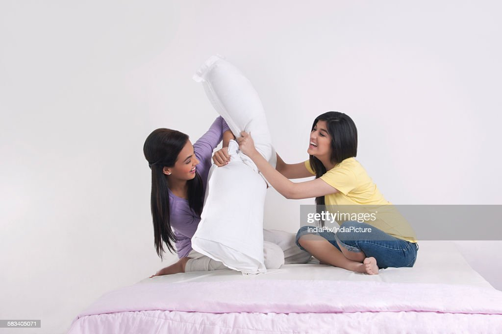 Two sisters having a pillow fight : Stock Photo