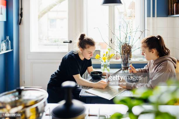 two sisters having breakfast in kitchen together - routine stock pictures, royalty-free photos & images