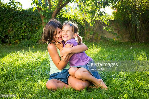 Two sisters having fun ogether on a meadow