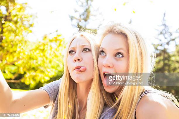 two sisters having fun outdoors in a city park in autumn taking selfies of themselves and making funny faces - woman long tongue stock photos and pictures