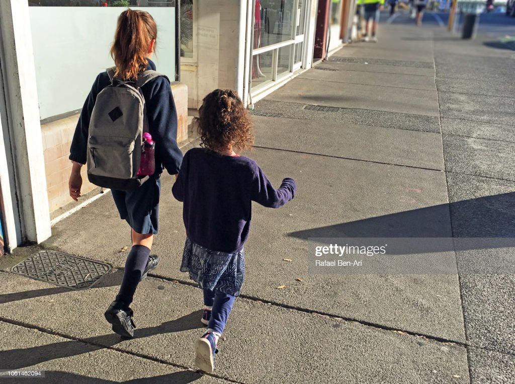 Two Sisters Holding Hands and Walking Together on City Street to School : Stock Photo