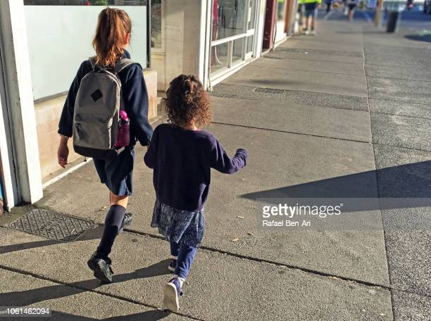 Two Sisters Holding Hands and Walking Together on City Street to School