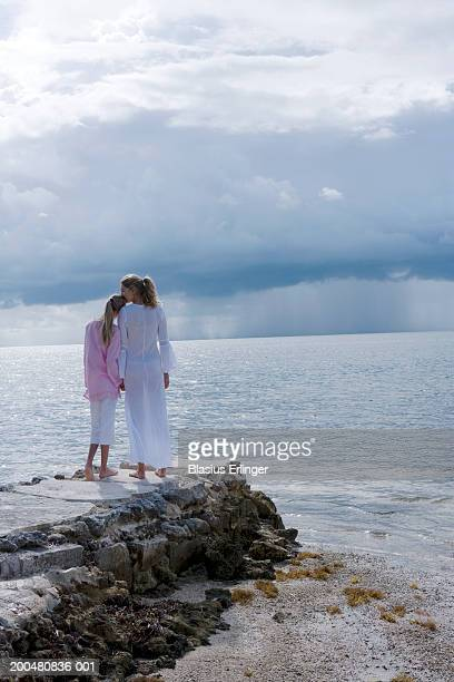 two sisters (11-18) holding hands overlooking sea, rear view - blasius erlinger stock pictures, royalty-free photos & images