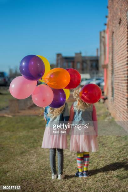 Two sisters holding hands with bunch of colourful balloons, rear view
