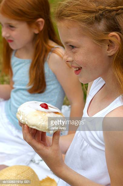Two sisters (6-9) holding iced buns, outdoors