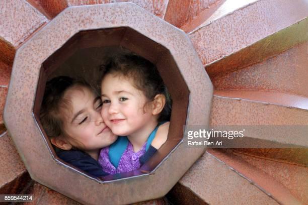 Two sisters hug outdoors