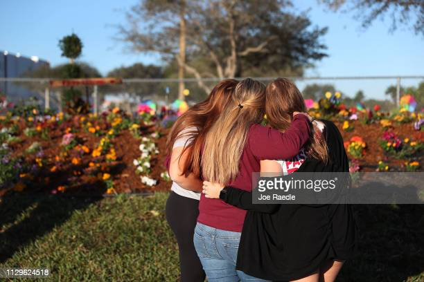 Two sisters hug their mother while looking on at a memorial setup for those killed at Marjory Stoneman Douglas High School on February 14 2019 in...