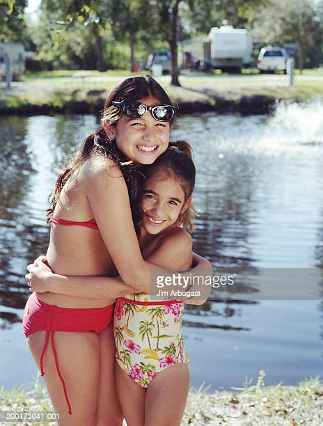 Two sisters (7-11) hugging near water, smiling, portrait