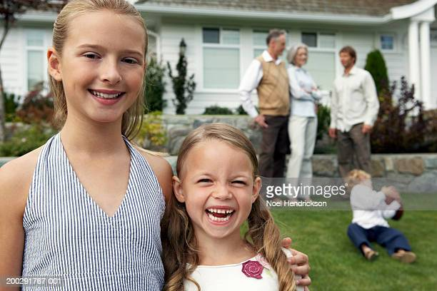 Two sisters (6-12 years) in garden, smiling, portrait, family in background