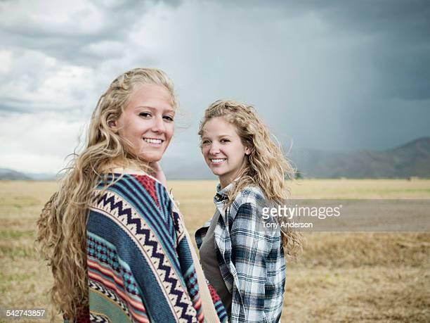 Two sisters in open field under stormy skies