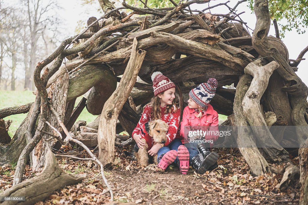 Two sisters in winter clothes in log den with dog : Stock Photo