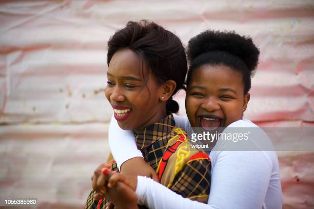 two sisters laughing together - south african culture stock photos and pictures