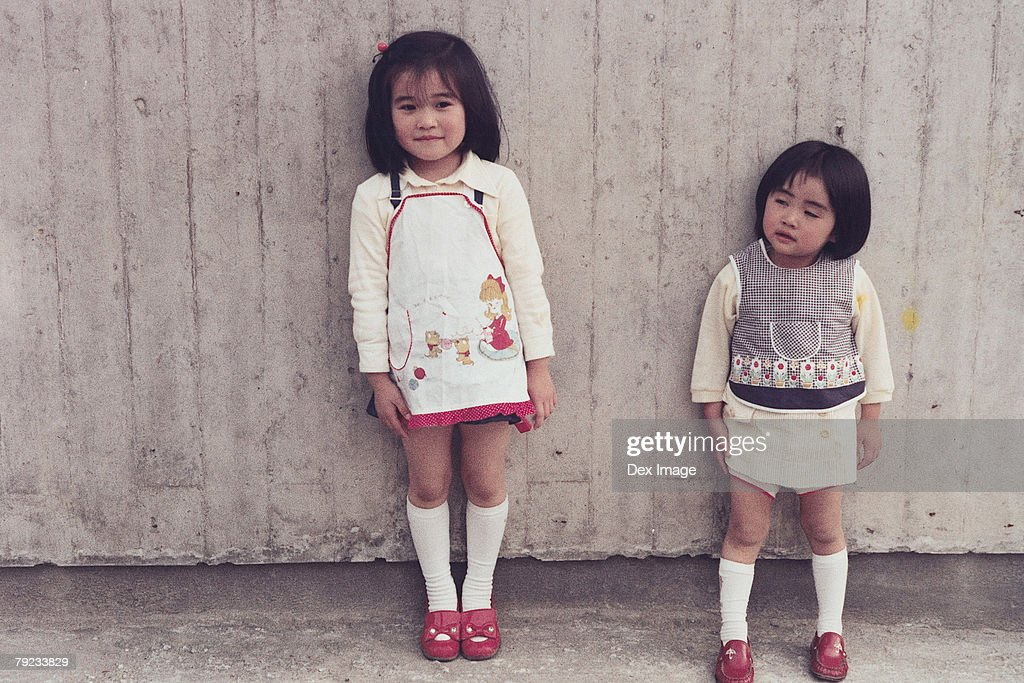 Two sisters leaning against the wall : Stock Photo