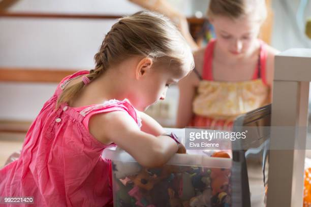 two sisters looking at small toys in a toy box - toy box stock pictures, royalty-free photos & images