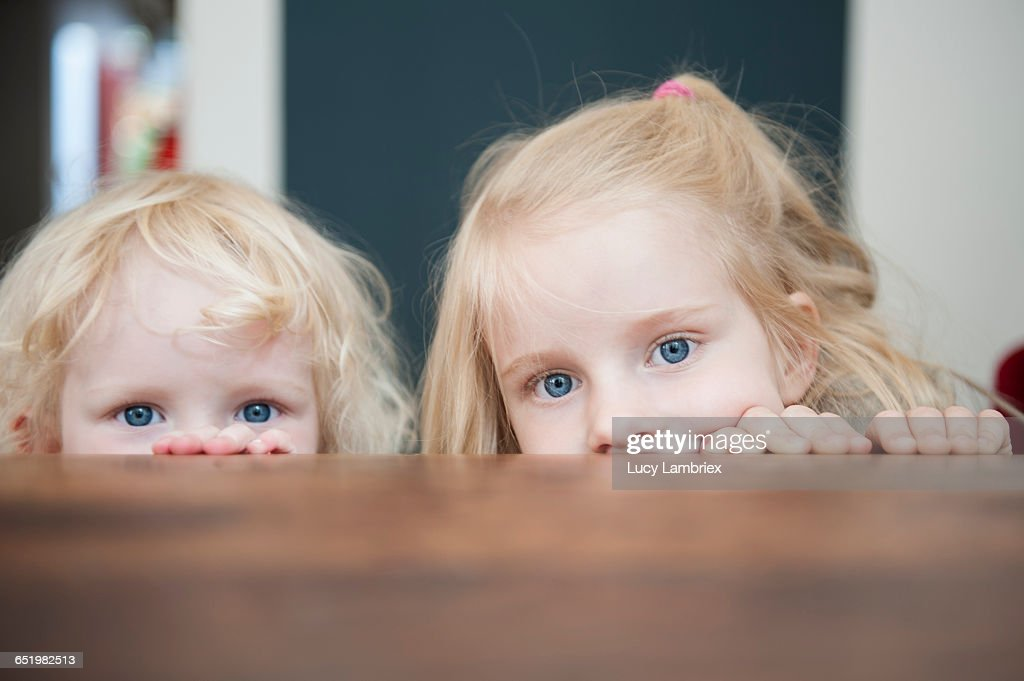 Two sisters looking just above the table : Stock Photo