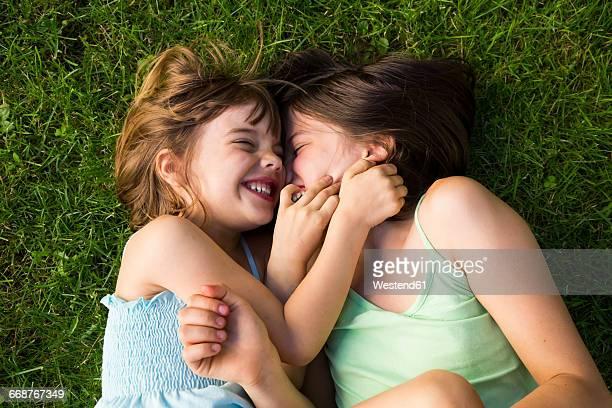 two sisters lying in meadow having fun - mädchen stock-fotos und bilder