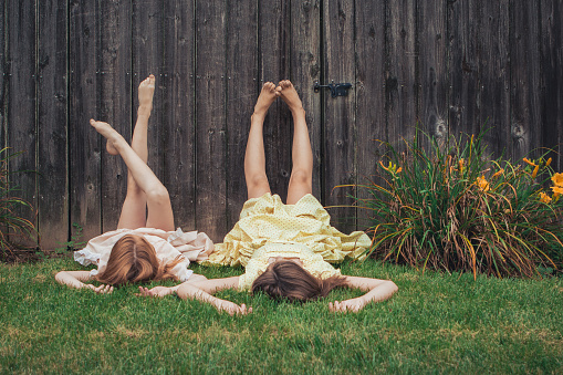 two sisters lying on the grass - gettyimageskorea