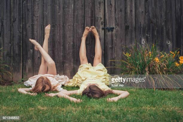 two sisters lying on the grass - kind vor der pubertät stock-fotos und bilder