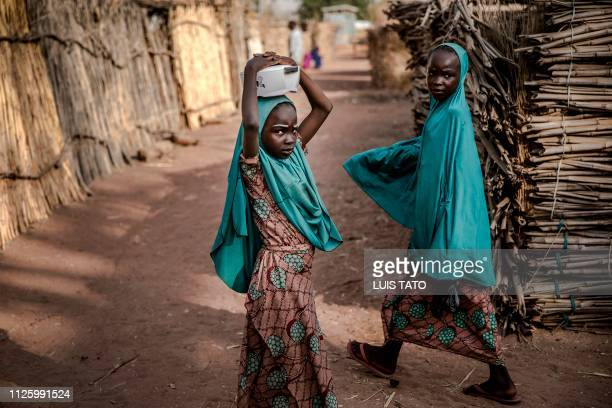 TOPSHOT Two sisters make their way home at Malkohi refugee camp in Jimeta Adamawa State Nigeria on February 19 four days ahead of the country's...