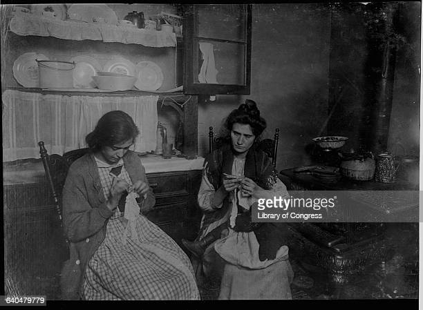 Two sisters one holding a baby on her lap make lace collars for a living in the kitchen of their New York City tenement apartment | Location 309 E...