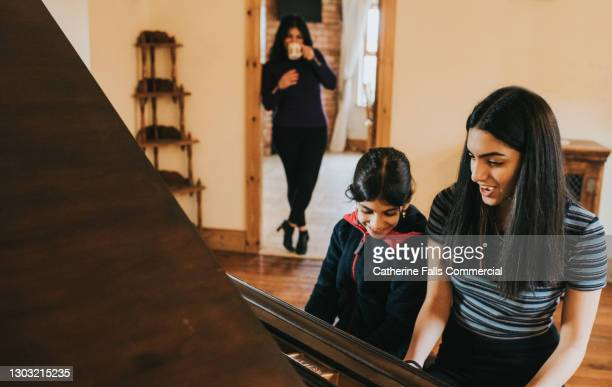 two sisters play the piano together while mum watches - theatrical performance stock pictures, royalty-free photos & images