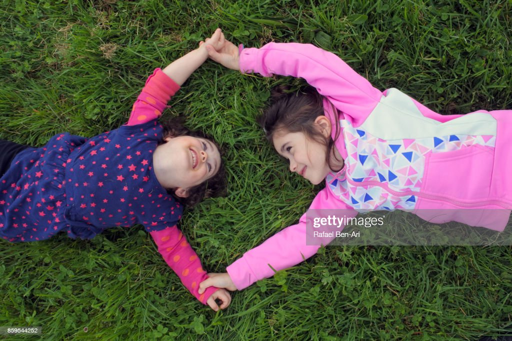Two sisters play together on green grass : Foto de stock