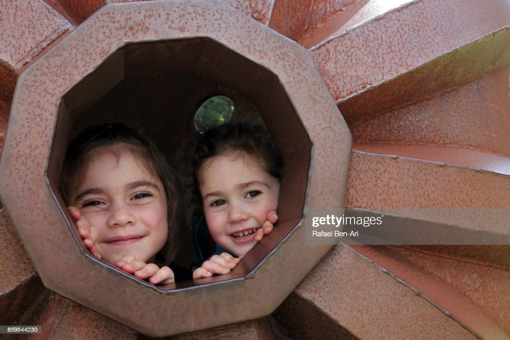 Two sisters play together outdoors : Stock Photo