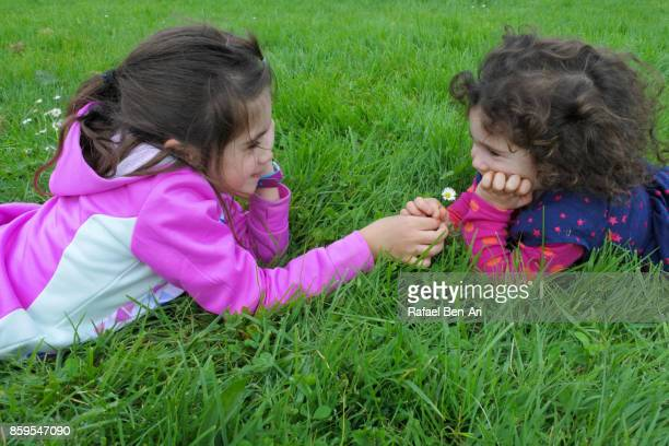 Two sisters play with flowers outdoors