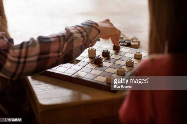 two sisters playing draughts board game on a dining table - chequers stock pictures, royalty-free photos & images