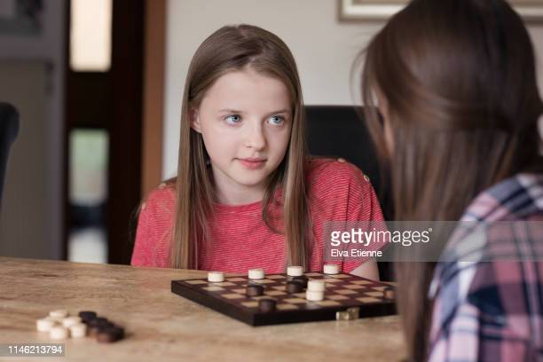 two sisters playing draughts board game on a dining table - tabuleiro de xadrez imagens e fotografias de stock
