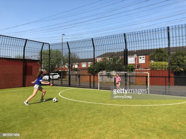 two sisters playing football together on urban pitch - penalty kick stock pictures, royalty-free photos & images